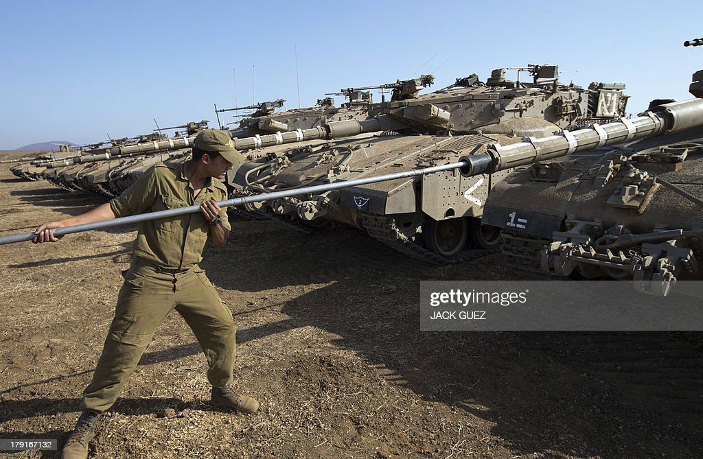 An Israeli soldier checks a Merkava tank stationed in the Israeli-occupied Golan Heights along the border with Syria on September 1, 2013. The Israeli cabinet authorised on August 28 a partial call-up of army reservists amid growing expectations of a foreign military strike on neighbouring Syria, army radio reported. The unspecified number of troops are attached to units stationed in the north of the country, which borders both Lebanon and the Golan Heights.