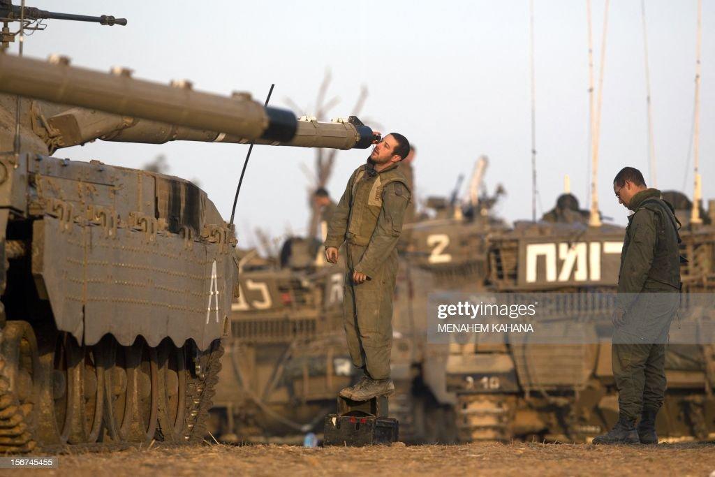 An Israeli soldier checks a tank barrel at an Israeli army deployment area near the IsraelGaza Strip border on November 20 as talks aimed at securing...