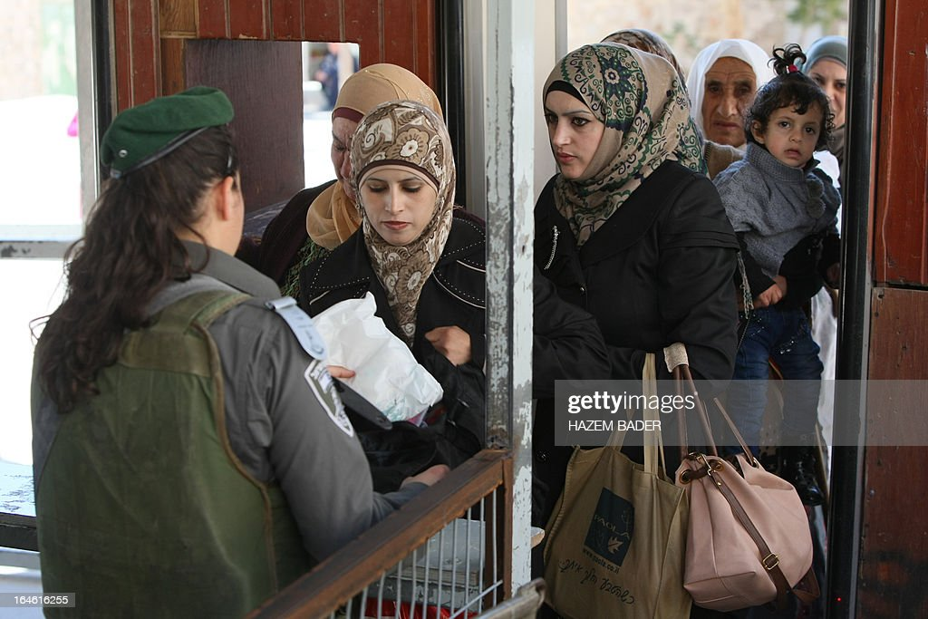 An Israeli soldier checks Palestinians as they cross an Israeli checkpoint in the occupied West Bank city of Hebron to go to the Ibrahimi Mosque or the Tomb of the Patriarch on March 25, 2013. The Ibrahimi Mosque and the Tomb of the Patriarch will be closed to Muslims on March 27 and 28 due to the Jewish holiday of Pesach (Passover).