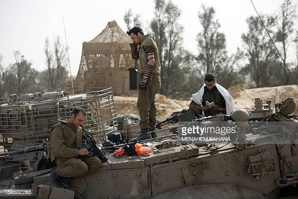 An Israeli soldier cleans his gun as other pray on their tank stationed at the IsraeliGaza Strip border on November 16 2012 Israeli officials said...