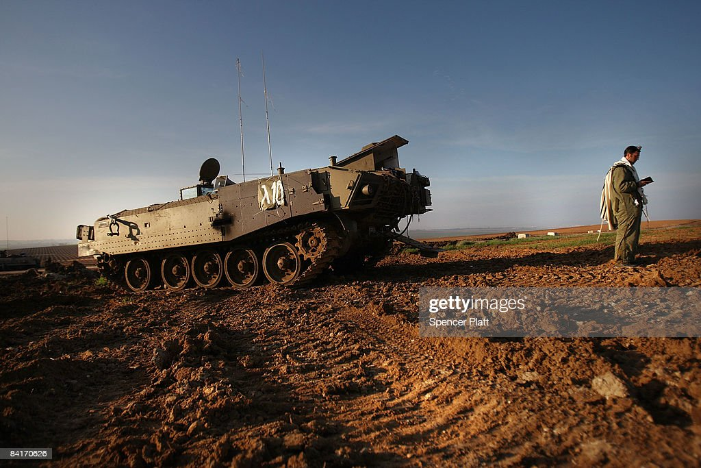 An Israeli soldier conducts his morning prayers while next to his Armored Personnel Carrier along the IsraeliGaza border January 5 2009 in Israel...