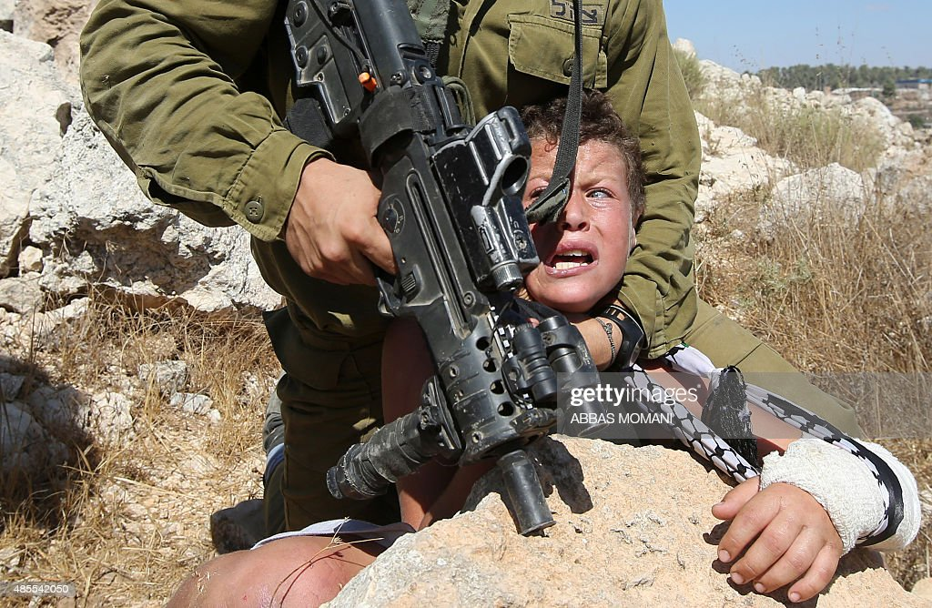 An Israeli soldier controls a Palestinian boy during clashes between Israeli security forces and Palestinian protesters following a march against...