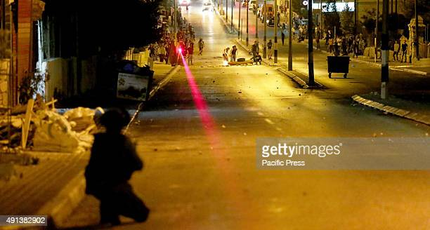 An Israeli soldier crouches in the street of Bethlehem in the West Bank looking on at Palestinian demonstrators Palestinians across the West Bank and...
