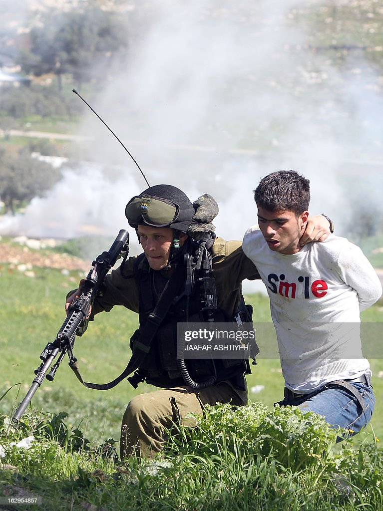 An Israeli soldier detains a Palestinian during a rally marking the 46th anniversary of the foundation of the Popular Front for the Liberation of Palestine (PFLP), a Palestinian Marxist-Leninist and revolutionary leftist organization founded in 1967, as clashes broke out between Israeli security and protesters in the northern city of Nablus, in the Israeli occupied West Bank, on March 2, 2013.