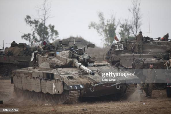 An Israeli soldier directs a tank in a deployment area on November 19 2012 on Israel's border with the Gaza Strip The death toll has risen to at...