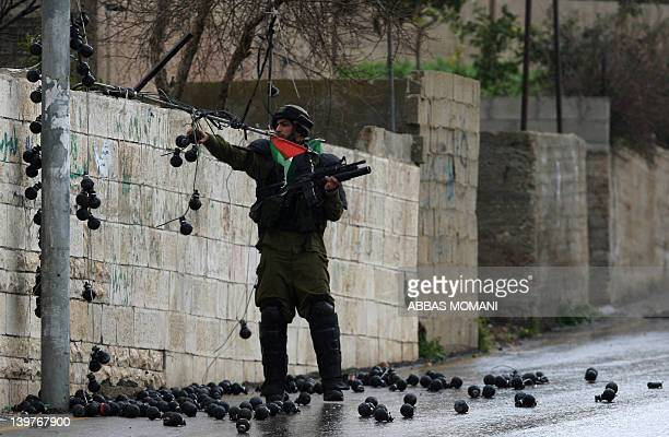 An Israeli soldier dismantles a display of empty tear gas canisters put by a Palestinian family outside their house during a weekly Palestinian...