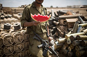 An Israeli soldier eats a piece of watermelon near the IsraeliGaza border on July 25 2014 near Israel's border with the Gaza Strip As operation...