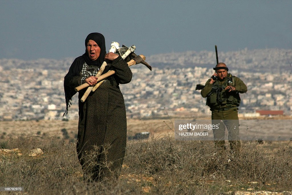 An Israeli soldier evacuates a Palestinian land owner trying to farm on her land near the Jewish settlement of Sosia, in the village of Yatta south of the West Bank city of Hebron on December 29, 2012. Palestinian farmers are restricted from cultivating their land in the disputed area near the city of Hebron due to the Israeli settlements and military zone nearby. AFP PHOTO / HAZEM BADER