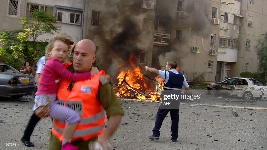 An Israeli soldier evacuates a young girl from a site hit by a rocket launched by Palestinian militants from the Gaza Strip in the southern Israeli city of Beer Sheva on November 20, 2012. Israeli leaders discussed an Egyptian plan for a truce with Gaza's ruling Hamas, reports said, before a mission by the UN chief to Jerusalem and as the toll from Israeli raids on Gaza rose over 100. AFP PHOTO/DANNY SASSON ==ISRAEL OUT==