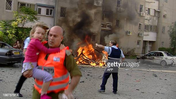 An Israeli soldier evacuates a young girl from a site hit by a rocket launched by Palestinian militants from the Gaza Strip in the southern Israeli...
