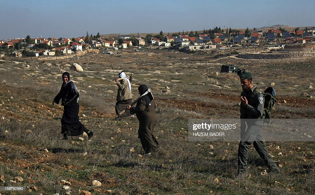 An Israeli soldier evacuates Palestinian land owners trying to farm on their land near the Jewish settlement of Sosia, in the village of Yatta south of the West Bank city of Hebron on December 29, 2012. Palestinian farmers are restricted from cultivating their land in the disputed area near the city of Hebron due to the Israeli settlements and military zone nearby.