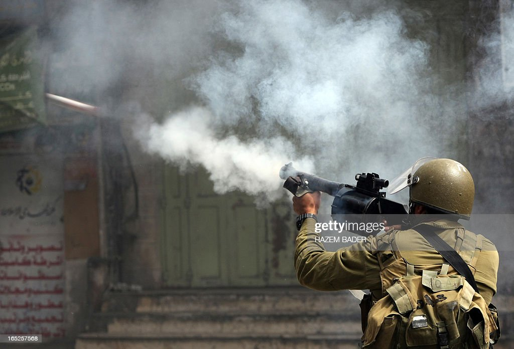 An Israeli soldier fires a tear gas canister during clashes with Palestinian stone throwers in the West Bank city of Hebron following the death of a Palestinian prisoner on April 2, 2013. The Palestinian leadership blamed Israel for the death of Maisara Abu Hamdiyeh, a long-term prisoner with cancer, hiking tensions over a tinderbox issue closely followed on the Palestinian street.