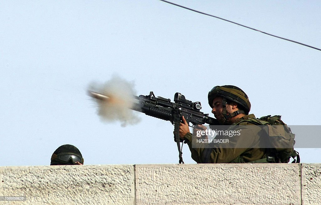 An Israeli soldier fires a tear gas canister towards Palestinian stone throwers on route 60, mainly used by Israeli settlers, in the West Bank village of Beit Omar, on November 16, 2012 . Thousands of angry Palestinians rallied across the West Bank, urging Hamas militants to 'bomb Tel Aviv' as Israel pursued a relentless air campaign on the Gaza Strip.