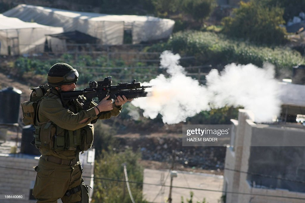 An Israeli soldier fires a tear gas canister towards Palestinian protestors (unseen) during clashes in the West Bank village of Beit Omar on November 15, 2012, following Israel's ongoing military operation in the Gaza Strip. Israeli air strikes have killed 13 Gazans, including top Hamas commander Ahmed Jaabari, as three Israelis die when a rocket strikes a house, in the latest flareup of tit-for-tat fighting.