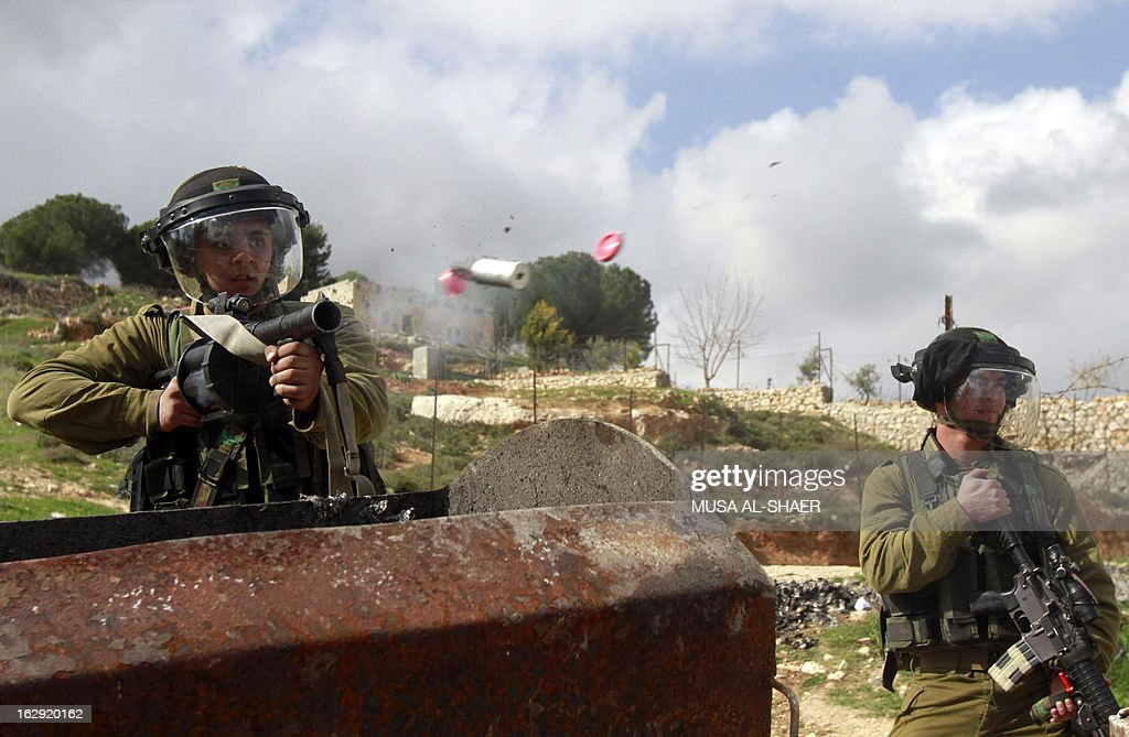 An Israeli soldier fires a tear gas grenade towards Palestinian youths throwing stones during clashes between hundreds of youths and Israeli security in the West Bank village of al-Khader near the West Bank town of Bethlehem, on March 1, 2013.