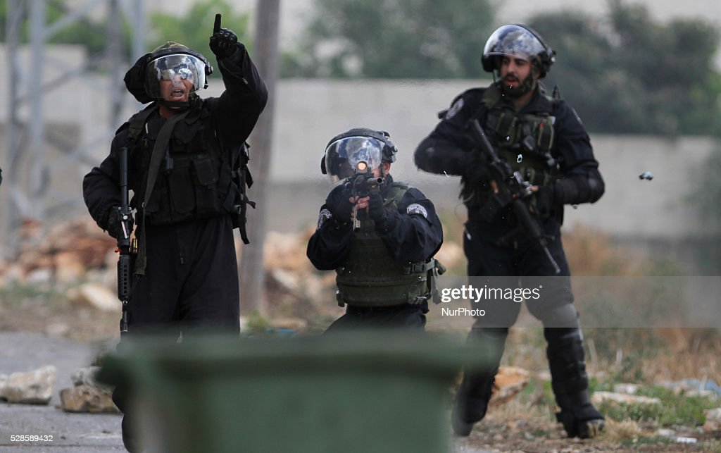 An Israeli soldier fires bullets at Palestinian protesters during a protest against the expanding of Jewish settlements in Kufer Qaddom village, near the West Bank city of Nablus. May 6, 2016.