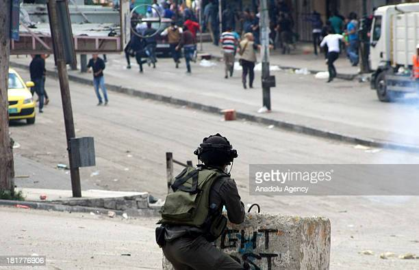 An Israeli soldier fires rubber bullets at Palestinian protesters as Jewish settlers erect a protest tent in front of the house of the Palestinian...