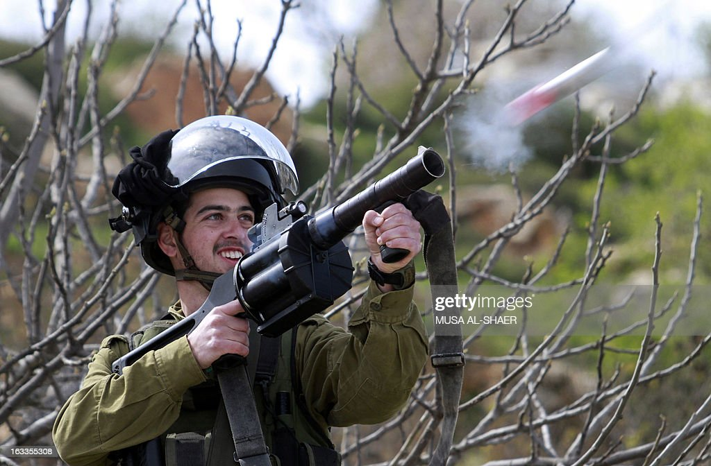 An Israeli soldier fires tear gas towards Palestinian protesters during clashes in the West Bank village of al-Khader near the West Bank town of Bethlehem, on March 8, 2013. Figures published by Israeli rights group B'Tselem at the end of January show there are currently 4,500 Palestinians being held by Israel, of whom 159 are being held in administrative detention. AFP PHOTO/MUSA AL-SHAER