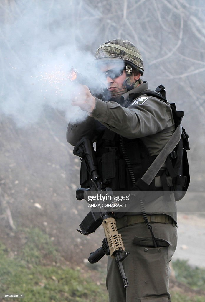 An Israeli soldier fires tear gas towards Palestinians during clashes as they set up a new camp to protest against Jewish settlements near the West Bank village of Burin on February 2, 2013.AFP PHOTO/AHMAD GHARABLI