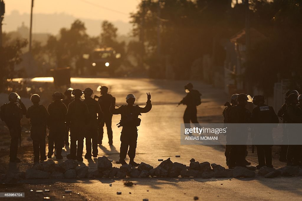 An Israeli soldier flashes the sign for victory during clashes with Palestinian demonstrators in the West Bank village of Silwad, near Ramallah, following a demonstration in support of the Hamas militants' resistance in the Gaza Strip and against the killing of children by Israeli strikes on the Palestinian enclave on August 22, 2104. Hamas gunmen executed 18 people accused of collaborating with Israel in Gaza City as Palestinian mortar fire killed a four-year-old Israeli boy on Day 46 of a devastating war. AFP PHOTO / ABBAS MOMANI