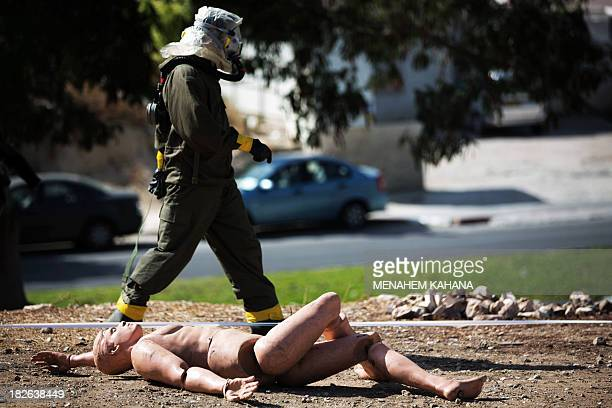 An Israeli soldier from the army's Home Front Command wearing a chemical warfare suit walks past a dummy of an injured man as he takes part in a...