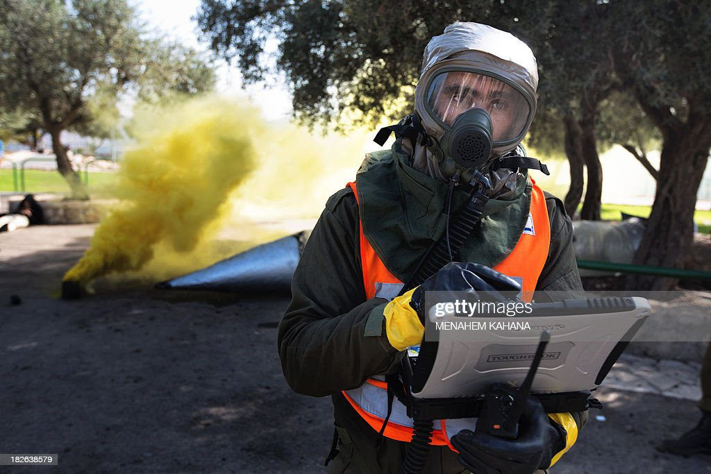 An Israeli soldier from the army's Home Front Command wearing a chemical warfare suit takes part in a defence drill simulating a chemical missile attack in the central Israeli city of Beit Shemesh, on October 2 2013.