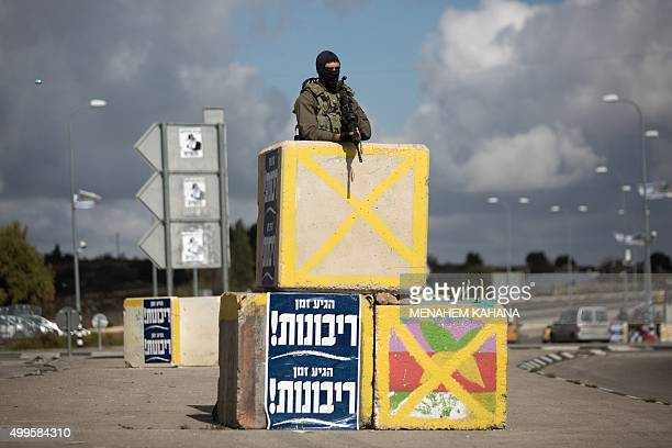 An Israeli soldier from the elite infantry unit stands guard at the Gush Etzion junction in the Israeli occupied West Bank on the main road between...