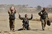 An Israeli soldier gestures in relief as he walks with comrades near the border between Israel and the Gaza Strip after returning from the...