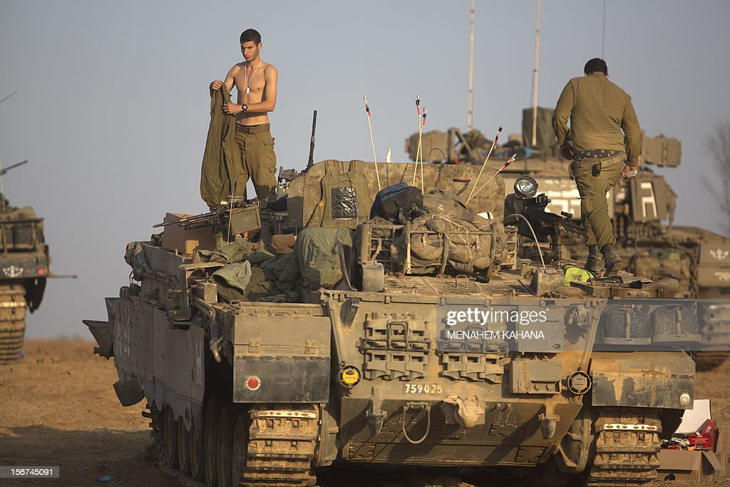 An Israeli soldier gets dressed on top of a tank at an Israeli army deployment area near the IsraelGaza Strip border on November 20 as talks aimed at...