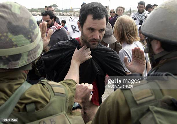 An Israeli soldier grabs the shirt of a protesting activist during a demonstration attended by Palestinian Israeli and international activists...