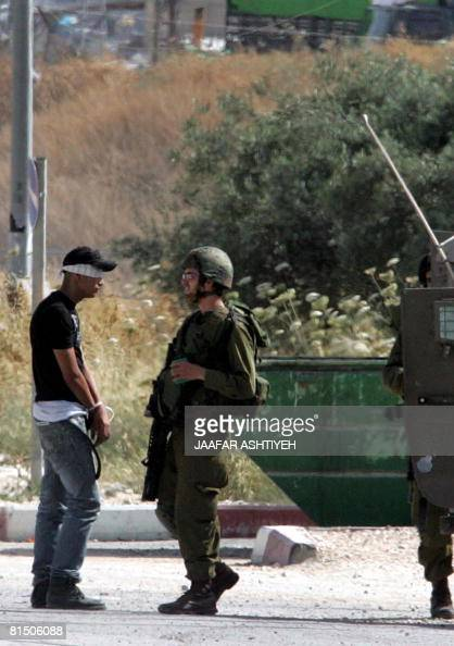 An Israeli soldier guards a blindfolded and handcuffed Palestinian youth after he was detained allegedly for carrying explosives on Hawara checkpoint...