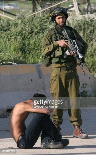 An Israeli soldier guards a detained Palestinian youth at the Hawara checkpoint near the West Bank city of Nablus on April 1 2008 The soldiers closed...