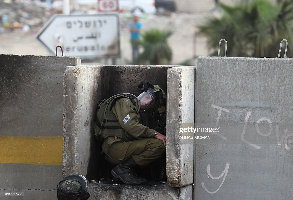 An Israeli soldier hides behind a cement block during clashes with Palestinian protestors following the funeral of man who died after inhaling tear gas smoke fired by Israeli forces during a weekly demonstration against Israeli occupation of Palestinian land, on March 15, 2013 in al-Ram near Ramallah.