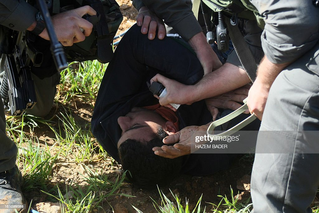 An Israeli soldier holds a pepper spray canister up close to the face of an arrested Palestinian lying on the ground as Palestinian activists tried to set up a new encampment to protest against settlement building in the Yatta, south of the West Bank city of Hebron on February 9, 2013. Soldiers dismantled tents that were being erected in two different areas near the town of Yatta, and forced activists to leave, the Palestinian witnesses said.