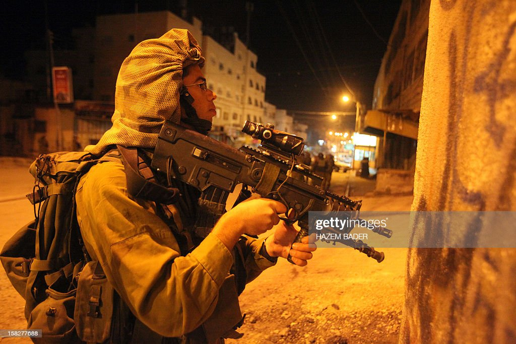 An Israeli soldier holds his gun during clashes with Palestinians in the West bank town of Hebron on December 12, 2012. Israeli border guards shot dead a Palestinian teenager, Mohammed Ziad Sulaima, aged 16, armed with a fake pistol in the city of Hebron, a police spokeswoman said, adding that clashes broke out after the shooting. AFP PHOTO / HAZEM BADER