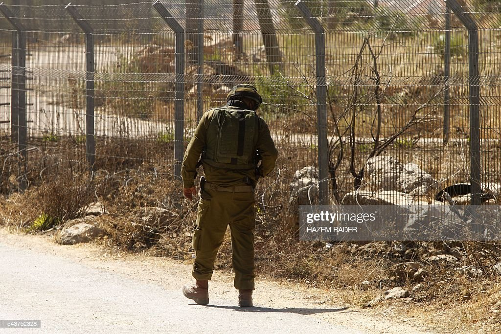 An Israeli soldier inspects a fence in the Jewish settlement of Kiryat Arba where a 13-year-old Israeli girl was fatally stabbed in her bedroom on June 30, 2016 in the occupied West Bank near the Palestinian city of Hebron. A Palestinian attacker broke into the Jewish settlement in the occupied West Bank, fatally stabbing a teenage girl and wounding a security guard before being shot dead, the army said. BADER
