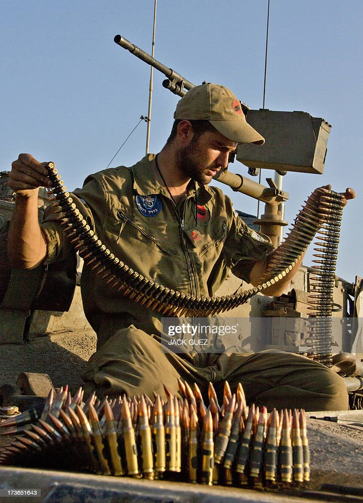 An Israeli soldier inspects an ammunition belt for a machine gun of a Merkava tank stationed in the Israeli-occupied Golan Heights on July 16, 2013, after mortar fire from inside war-torn Syria exploded in northern Golan, near the border with Syria earlier in the day causing several wildfires to break out. The apparently stray rounds struck as Syrian rebels and regime forces battled near Quneitra which lies in no-man's land, an AFP correspondent reported. Israel, which remains technically at war with Syria, seized 1,200 square kilometres (460 square miles) of the strategic plateau during the 1967 Six-Day War, which it later annexed in a move never recognised by the international community.