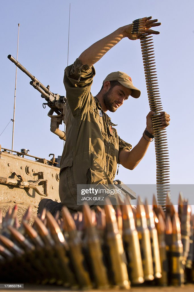 An Israeli soldier inspects an ammunition belt for a machine gun of a Merkava tank stationed in the Israeli-occupied Golan Heights on July 16, 2013, after mortar fire from inside war-torn Syria exploded in northern Golan, near the border with Syria earlier in the day causing several wildfires to break out. The apparently stray rounds struck as Syrian rebels and regime forces battled near Quneitra which lies in no-man's land, an AFP correspondent reported. Israel, which remains technically at war with Syria, seized 1,200 square kilometres (460 square miles) of the strategic plateau during the 1967 Six-Day War, which it later annexed in a move never recognised by the international community. AFP PHOTO / JACK GUEZ