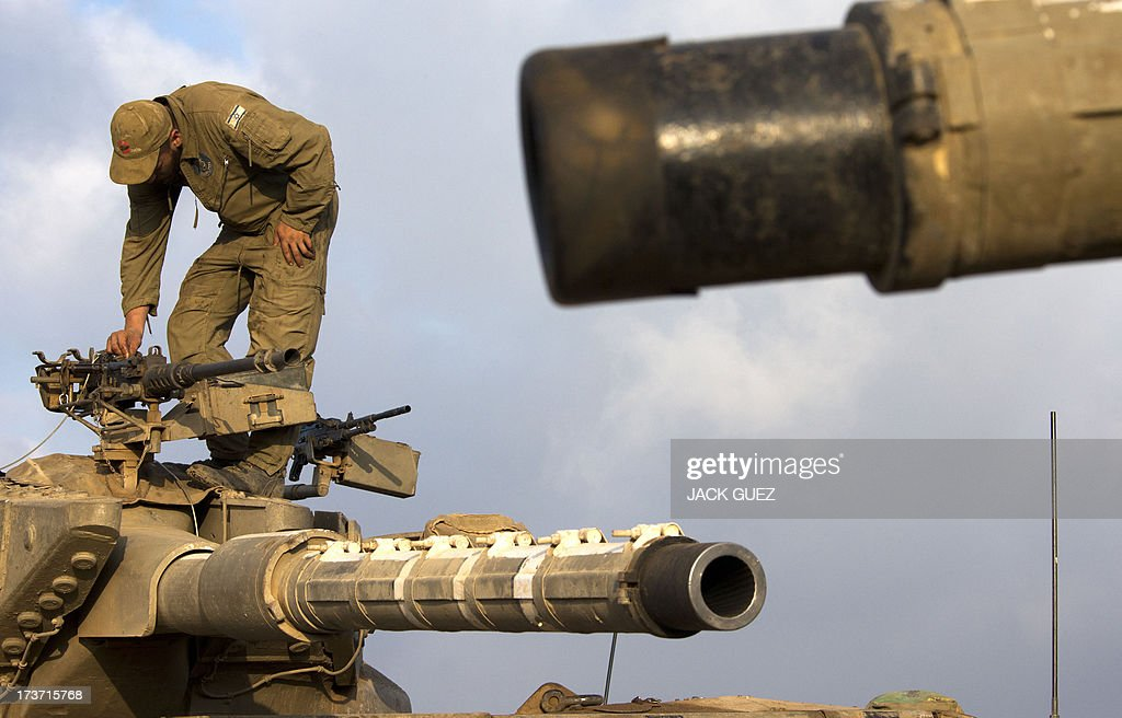 An Israeli soldier inspects the machine gun of a Merkava tank stationed in the Israeli-occupied Golan Heights along the border with Syria on July 17, 2013. Gunmen from Syria infiltrated a disused army outpost in the Israeli-occupied area of the Golan Heights just beyond the ceasefire line, a military spokeswoman said. The incident came a day after several mortar rounds hit the Israeli side of the Golan, causing several fires to break out along the ceasefire line as Syrian rebels battled regime forces near the Quneitra crossing.