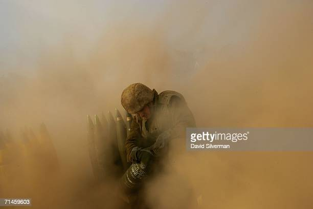 An Israeli soldier is surrounded with dust kicked up by a 155mm artillery cannon as it opens fire during a barrage against Hezbollah targets in South...