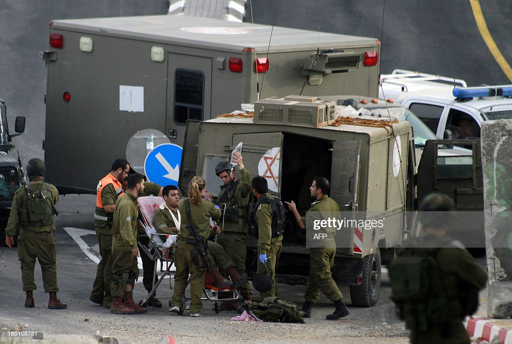 An Israeli soldier is treated after being injured during clashes following a rally marking Land Day in the al-khader village near the West Bank town of Bethlehem on March 30, 2013. The annual demonstrations mark the deaths of six Arab Israeli protesters at the hands of Israeli police and troops during mass protests in 1976 against plans to confiscate Arab land in the northern Galilee region.