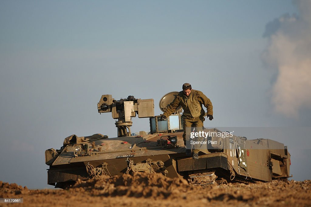An Israeli soldier jumps down from his Armored Personnel Carrier along the IsraeliGaza border January 5 2009 in Israel Heavy fighting continues...