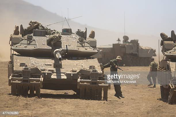 An Israeli soldier jumps from his tank during a military exercise in the center of the Israeliannexed Golan Heights on June 17 2015 An alliance of...