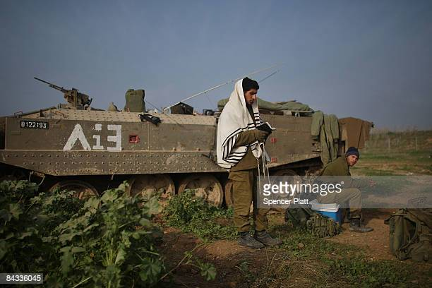 An Israeli soldier just back from Gaza prays beside his armored personnel carrier on January 17 2009 along the GazaIsraeli border in Israel While...