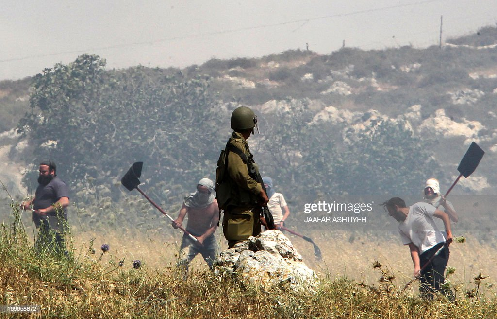 An Israeli soldier keeps watch as Jewish settlers try to extinguish the fire in a Palestinian farmer's field on the border with the Itzhar settlement on May 30, 2013 in village of Asira al-Qibiliya, in the Israeli-occupied West Bank. According to the Palestinian farmers, the settlers set fire to their fields but came to put away the flames once they realised it was getting out of control and could reach their settlement.