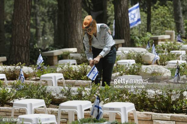 An Israeli soldier lays flowers on the graves of fallen soldiers at the Mount Herzel military cemetery in Jerusalem on April 30 a few hours ahead of...