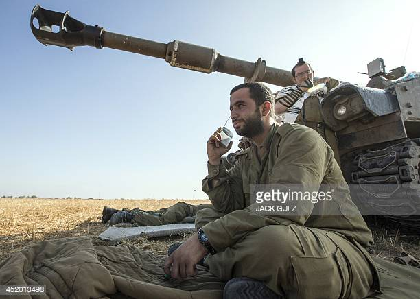 An Israeli soldier listens to a radio as he sits close to a 155mm mobil artillery cannon stationed along the southern Israeli border with the Gaza...