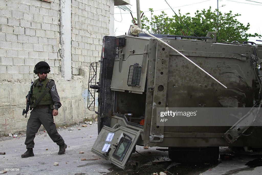 An Israeli soldier looks at an army vehicle which returned during during clashes with Israeli protesters following a rally marking Land Day in the al-khader village near the West Bank town of Bethlehem on March 30, 2013. The annual demonstrations mark the deaths of six Arab Israeli protesters at the hands of Israeli police and troops during mass protests in 1976 against plans to confiscate Arab land in the northern Galilee region.