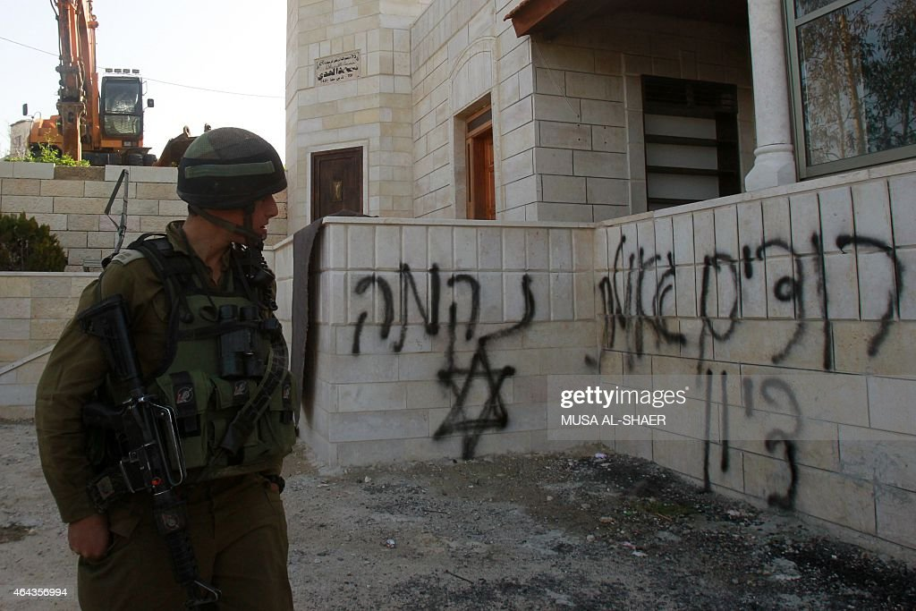 An Israeli soldier looks at graffiti on a wall near a mosque a day after it was set alight and covered with antiArab slogans in Hebrew in the West...
