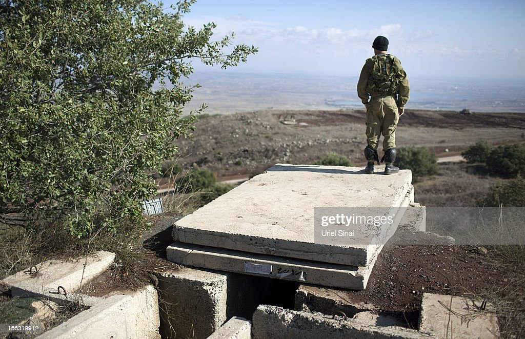 An Israeli soldier looks on as he stands on the border with Syria at the Israeli-annexed Golan Heights, overlooking the Syrian village of Breqa on November 13, 2012 in the Golan Heights. Tension remains high in the disputed Golan Heights after Israeli Defence Forces retaliated after mortar shells were fired into Israeli territory from Syria.